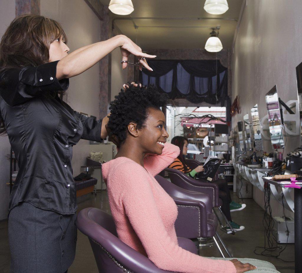 Hispanic hair stylist cutting African woman's hair : Stock Photo