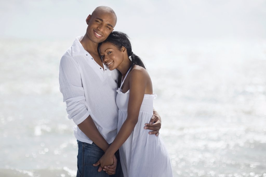 Stock Photo: 1589R-56006 Multi-ethnic couple hugging at beach
