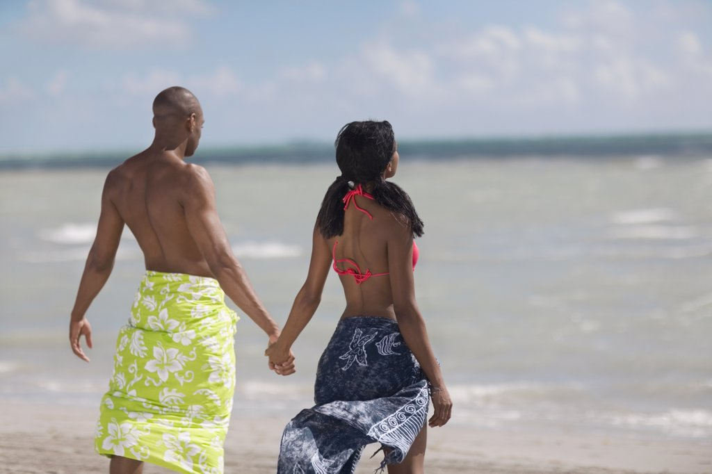 Multi-ethnic couple holding hands at beach : Stock Photo