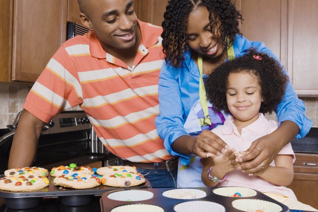 African parents and daughter making cupcakes : Stock Photo