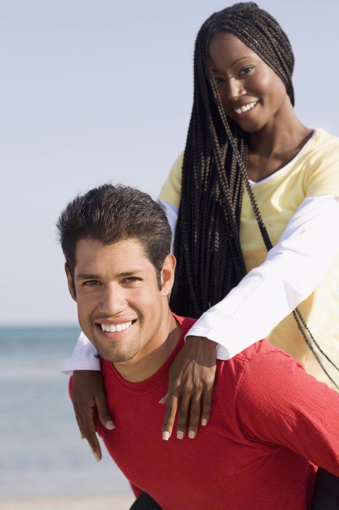 Stock Photo: 1589R-56234 Hispanic man giving girlfriend piggy back ride