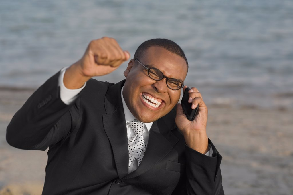 Stock Photo: 1589R-56253 African businessman cheering on cell phone