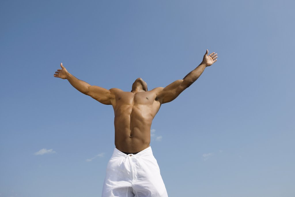 Bare-chested man with arms outstretched : Stock Photo