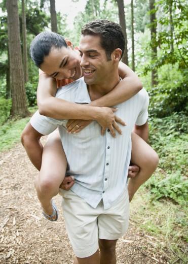 Stock Photo: 1589R-56427 Hispanic man giving girlfriend piggyback ride