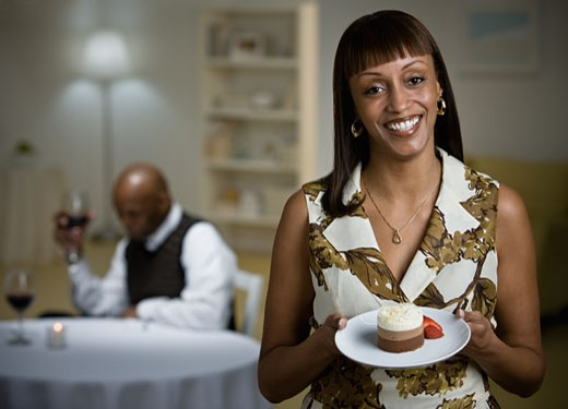 African woman holding plate of dessert : Stock Photo