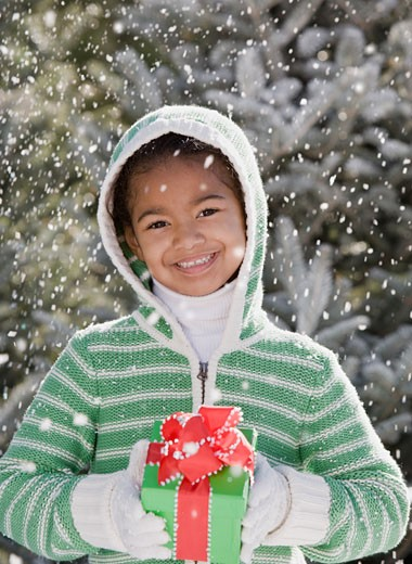 African girl holding gift in snow : Stock Photo