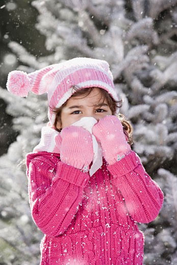 Stock Photo: 1589R-56602 Hispanic girl in snow blowing nose