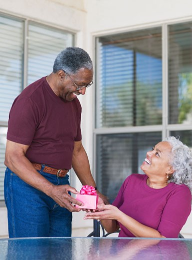 Senior African man giving gift to wife : Stock Photo