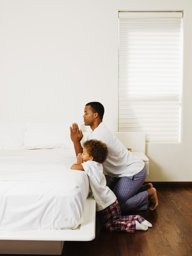 African father and son praying at bedside : Stock Photo