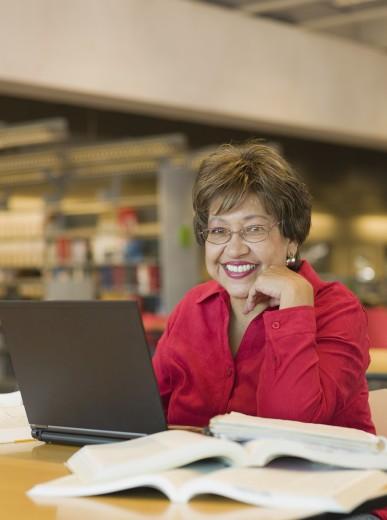 Senior Hispanic woman studying : Stock Photo