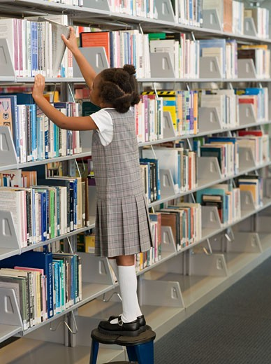 Stock Photo: 1589R-56840 African school girl taking library book off shelf