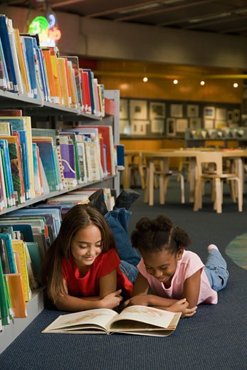 Stock Photo: 1589R-56850 Multi-ethnic girls reading library book