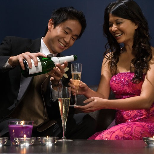 Asian man pouring champagne for girlfriend : Stock Photo