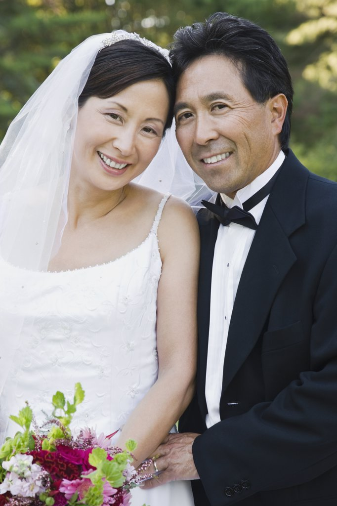 Asian newlyweds hugging : Stock Photo