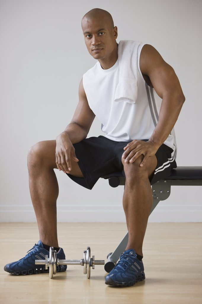 African man sitting on weight bench : Stock Photo