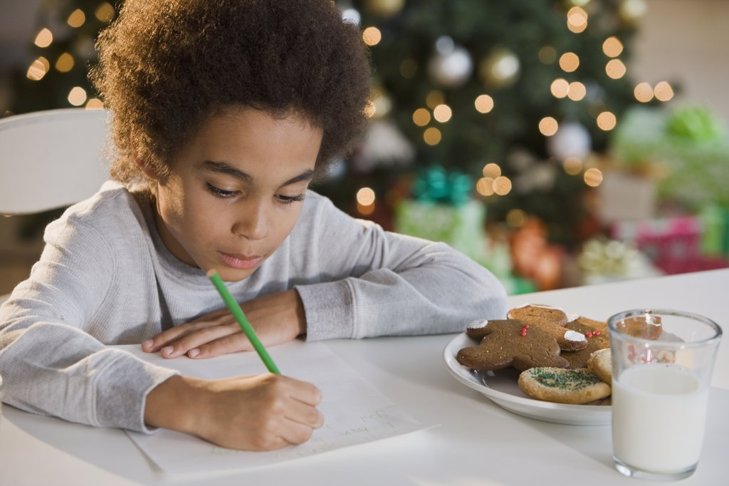 Mixed Race boy writing letter to Santa Claus : Stock Photo
