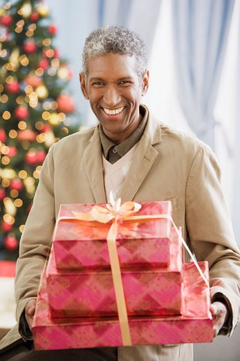 Stock Photo: 1589R-57639 African man holding Christmas gifts