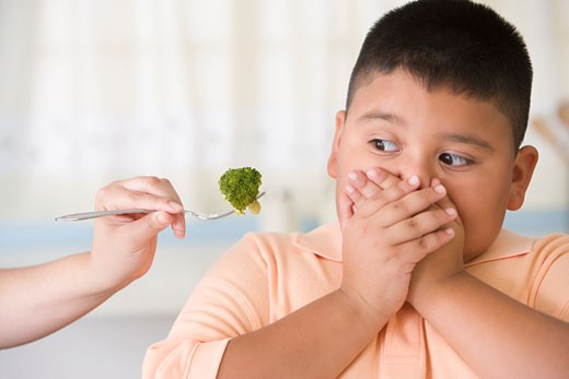 Stock Photo: 1589R-57694 Hispanic boy covering mouth next to broccoli