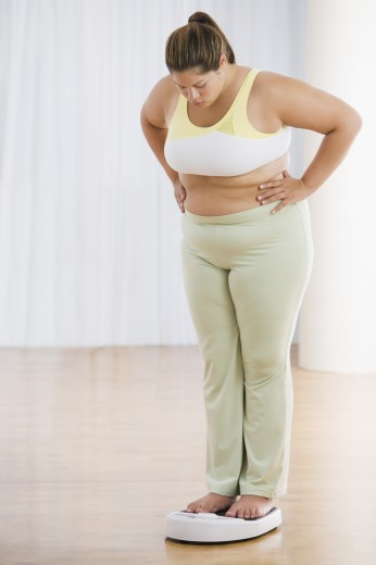 Stock Photo: 1589R-57751 Overweight Hispanic woman on scale