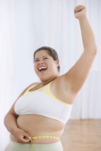 Overweight Hispanic woman measuring waist and cheering : Stock Photo