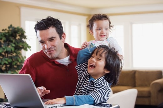 Stock Photo: 1589R-57775 Mixed Race father and children looking at laptop