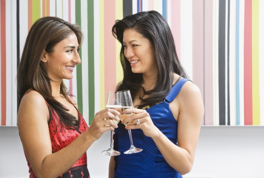 Multi-ethnic women toasting with champagne : Stock Photo