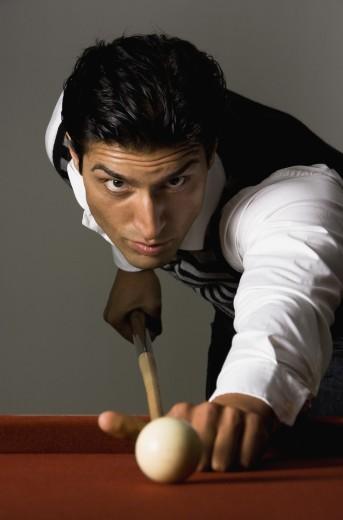 Mixed Race man playing billiards : Stock Photo