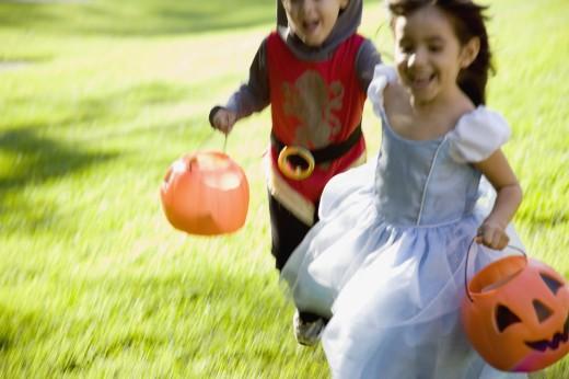 Hispanic siblings running in Halloween costumes : Stock Photo