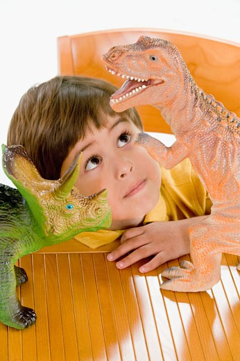 Stock Photo: 1589R-58002 Hispanic boy playing with toy dinosaurs