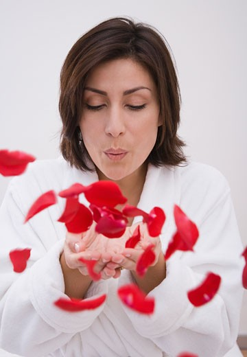 Hispanic woman blowing flower petals : Stock Photo