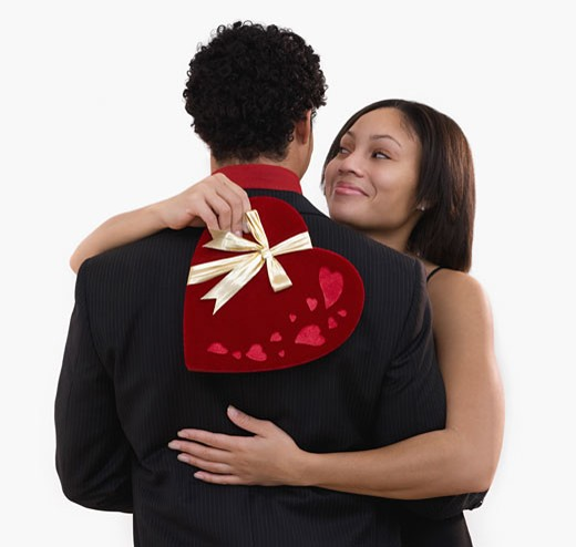 African woman holding valentine's gift and hugging boyfriend : Stock Photo