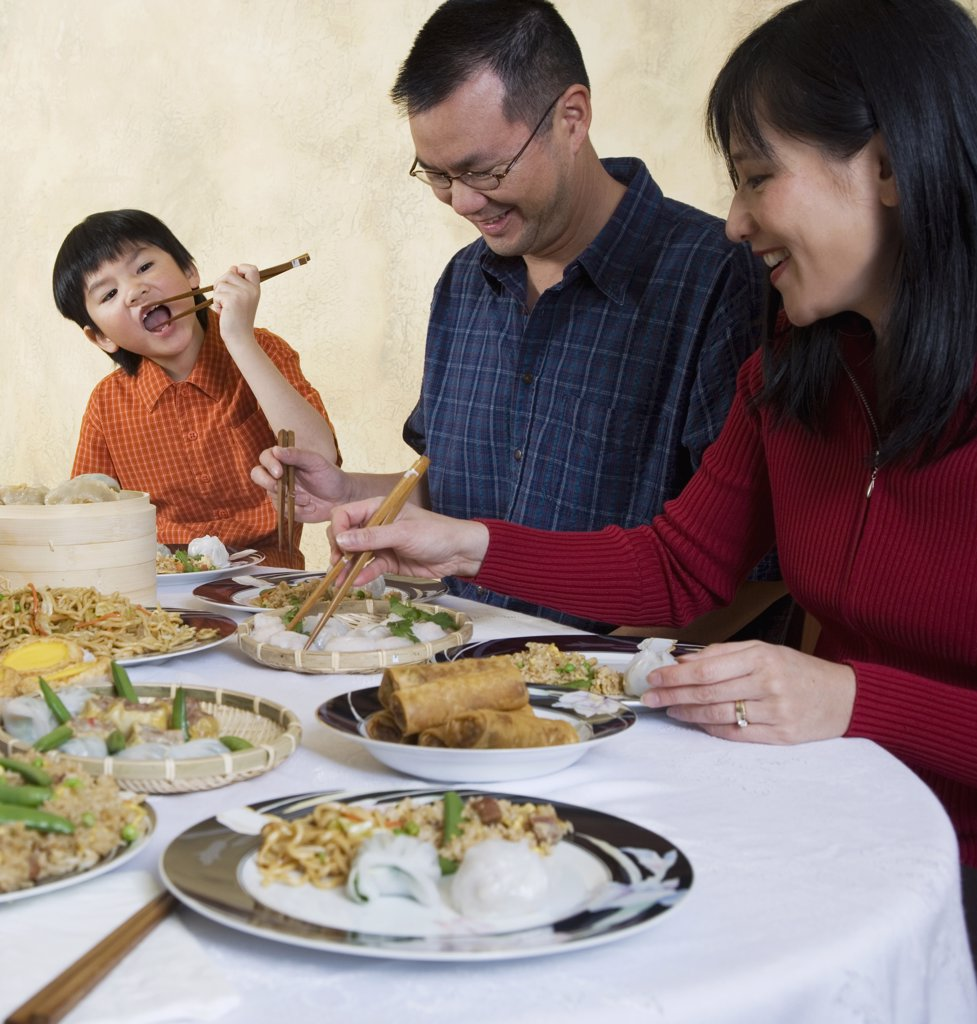 Asian Family Eating At Dinner Table Stock Photo 1589r