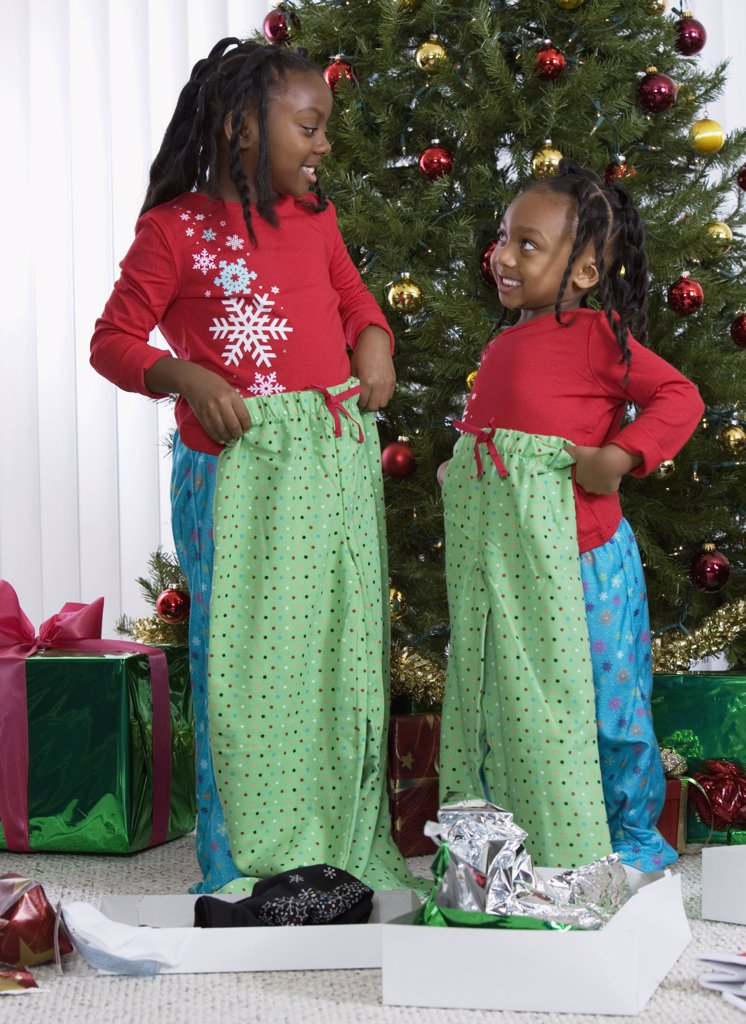 African sisters holding matching Christmas gifts : Stock Photo