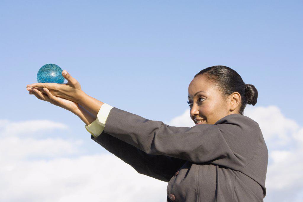 Hispanic businesswoman holding glass orb : Stock Photo