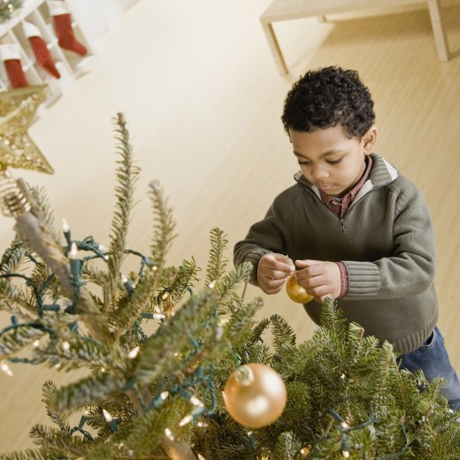 Mixed Race boy hanging ornament on Christmas tree : Stock Photo