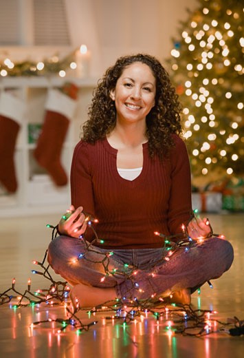 Stock Photo: 1589R-58567 Hispanic woman holding lit Christmas lights