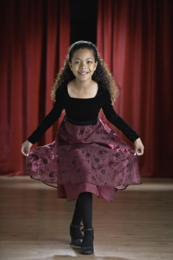 Mixed Race girl curtsying on stage : Stock Photo
