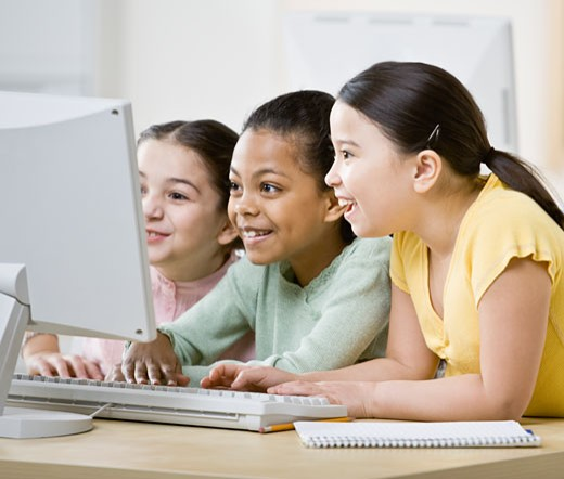 Multi-ethnic girls looking at computer : Stock Photo