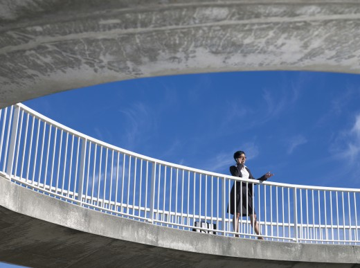 Mixed Race businesswoman leaning on railing : Stock Photo