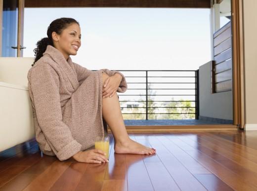 Stock Photo: 1589R-58853 Mixed Race woman in bathrobe sitting on floor