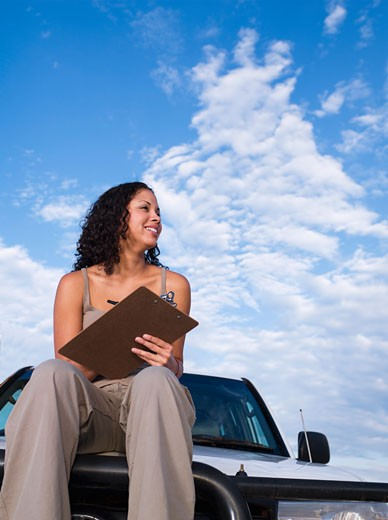 Stock Photo: 1589R-58902 Mixed Race woman on truck holding clipboard