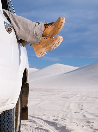 Woman's feet in work boots hanging out of truck window : Stock Photo