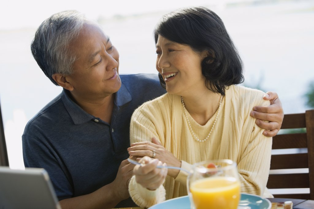 Asian couple smiling at each other : Stock Photo
