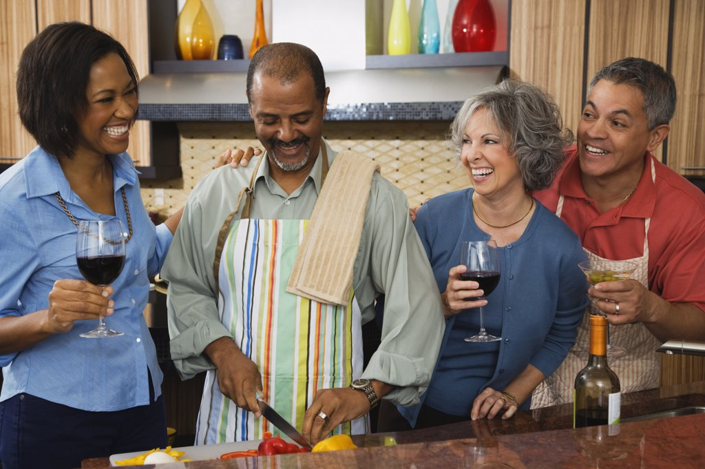 Multi-ethnic friends drinking wine and preparing food : Stock Photo