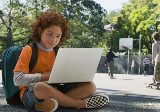 Mixed Race boy looking at laptop : Stock Photo