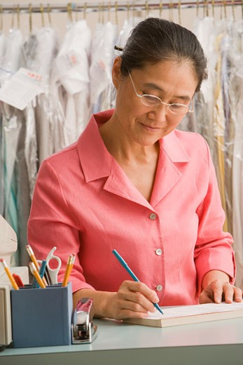 Asian female dry cleaner writing at counter : Stock Photo