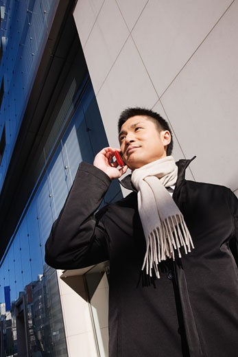 Asian man talking on cell phone : Stock Photo