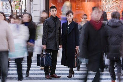 Asian businesspeople standing in crowd : Stock Photo