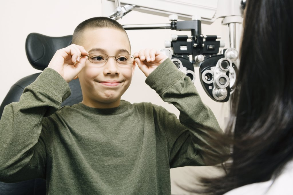 Stock Photo: 1589R-59685 Asian boy trying on eyeglasses