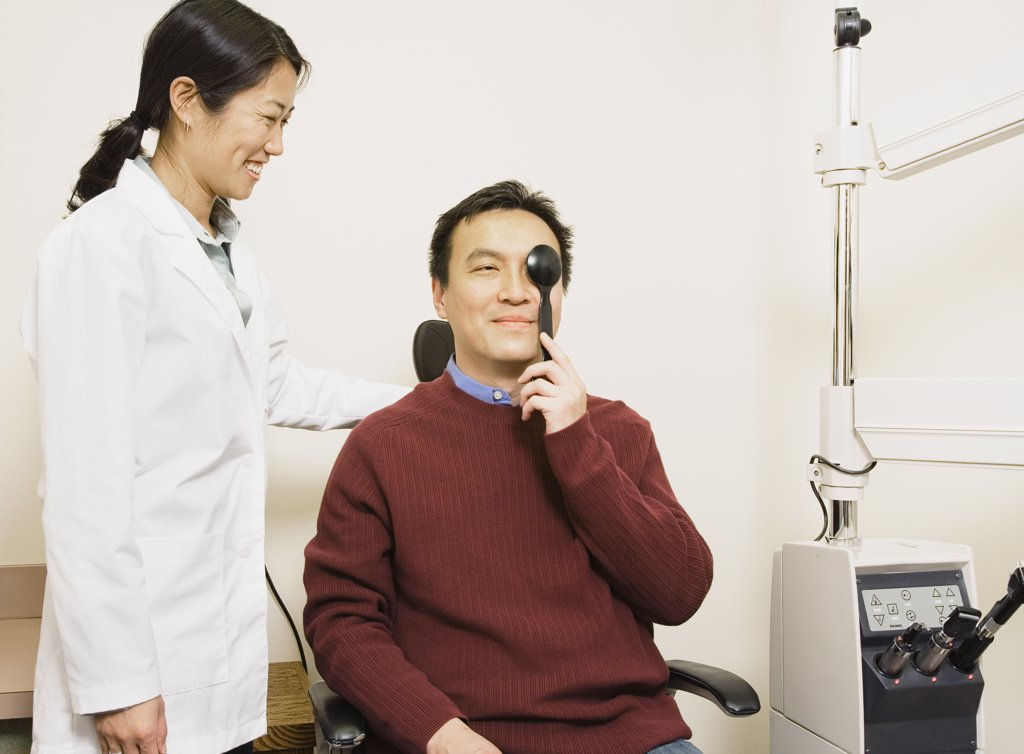 Asian female optometrist examining patient : Stock Photo